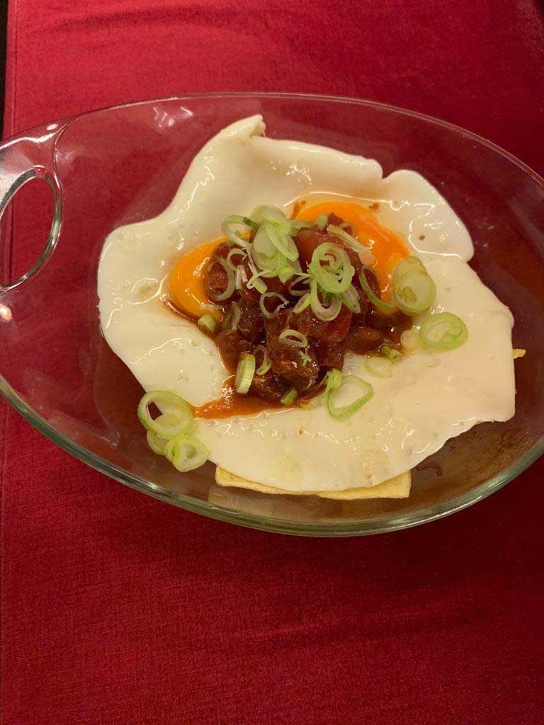 Huevos rotos con atún picante y cebolla china